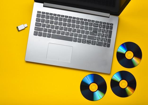 Ordinateur portable, lecteurs de cd, lecteur flash usb sur fond jaune. médias numériques modernes et obsolètes.