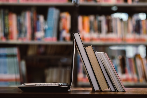 Ordinateur portable et livre sur le lieu de travail dans la salle de la bibliothèque