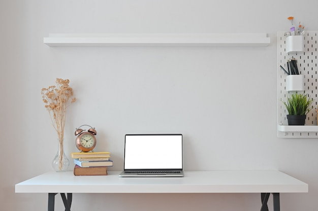 Ordinateur portable, livres, fleurs séchées, horloge, crayon et cache-pot avec tablettes et panneaux perforés au bureau.