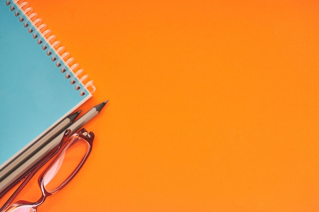 Ordinateur portable avec des lunettes et des crayons sur fond orange