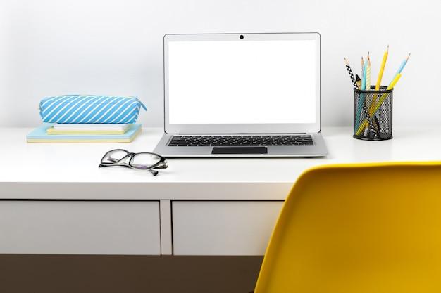 Ordinateur portable, lunettes et papeterie sur une table moderne blanche