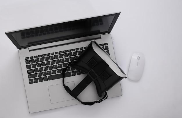 Ordinateur portable avec lunettes vr sur fond blanc. la réalité virtuelle. gadgets modernes. vue de dessus. mise à plat
