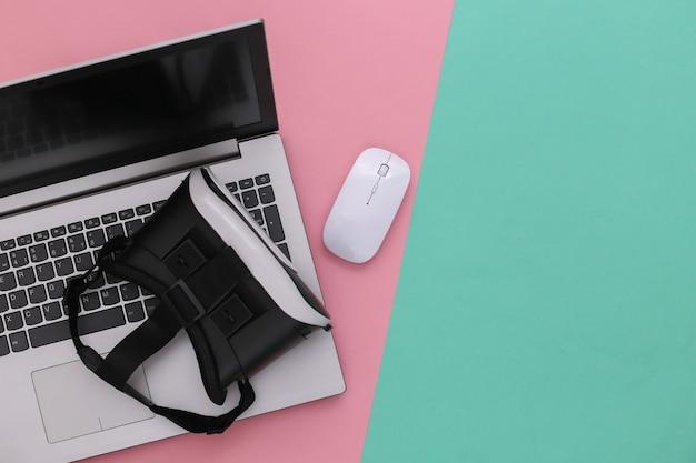 Ordinateur portable avec lunettes vr sur fond bleu-rose. la réalité virtuelle. gadgets modernes. vue de dessus. mise à plat