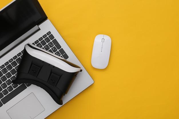 Ordinateur portable avec lunettes vr sur fond jaune. la réalité virtuelle. gadgets modernes. vue de dessus. mise à plat