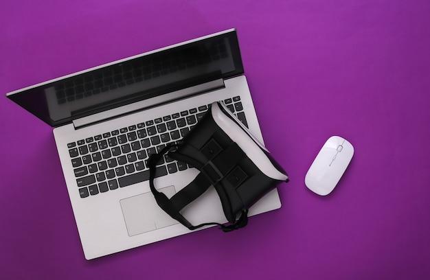 Ordinateur portable avec lunettes vr sur fond violet. la réalité virtuelle. gadgets modernes. vue de dessus. mise à plat