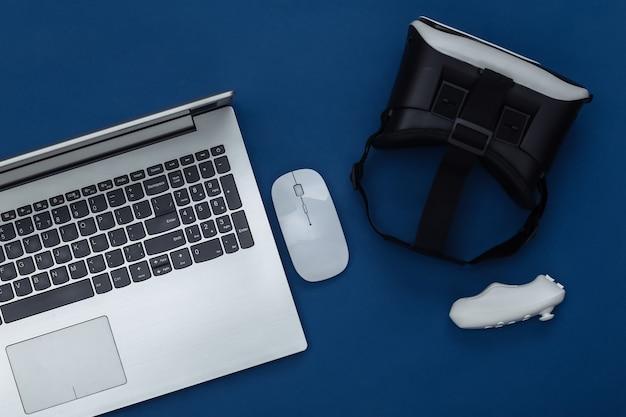 Ordinateur portable avec lunettes vr, joystick sur fond bleu classique. la réalité virtuelle. gadgets modernes, divertissement. vue de dessus. mise à plat