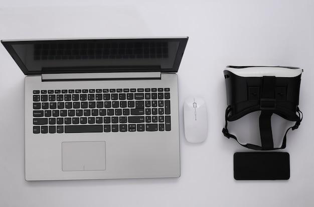 Ordinateur portable avec lunettes vr, smartphone sur fond blanc. la réalité virtuelle. gadgets modernes. vue de dessus. mise à plat