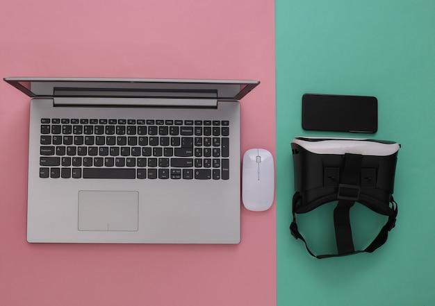 Ordinateur portable avec lunettes vr, smartphone sur fond bleu rose. la réalité virtuelle. gadgets modernes. vue de dessus. mise à plat
