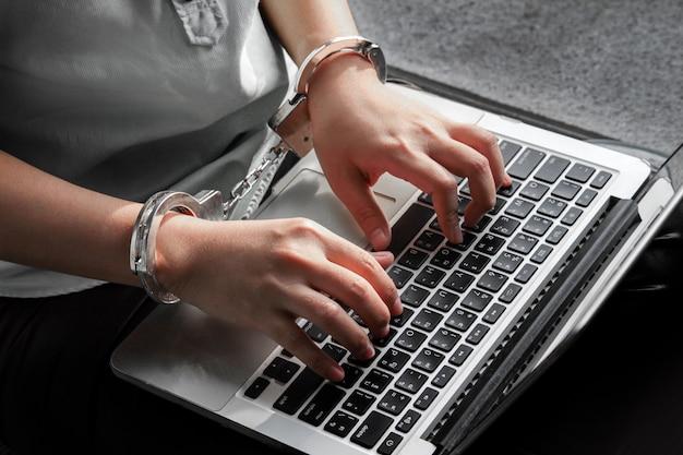 Ordinateur portable à la main pour le concept de bourreau de travail