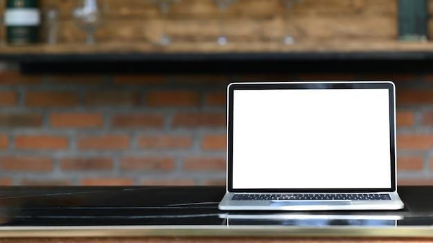 Ordinateur portable maquette avec écran blanc blanc mettant à l'extérieur sur la table moderne avec bar de cuisine classique comme
