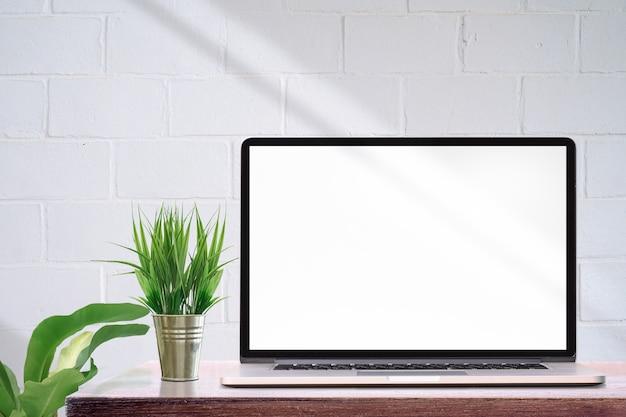 Ordinateur portable maquette avec écran blanc et plante d'intérieur sur table en bois, mur de briques blanches et espace copie.