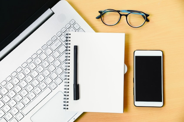 Ordinateur portable avec message smartphone et un stylo sur le bureau au bureau