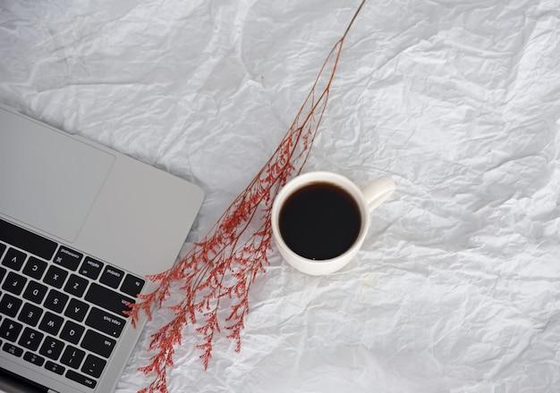 Ordinateur portable mis à côté d'une tasse de café en céramique et de fleurs séchées