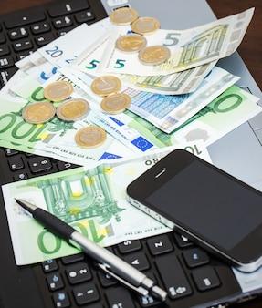 Ordinateur portable, mobile et argent liquide sur la table