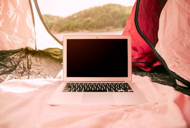 Ordinateur portable moderne dans une tente à l'extérieur