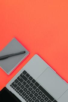 Ordinateur portable moderne gris et bloc-notes avec stylo sur une surface rouge