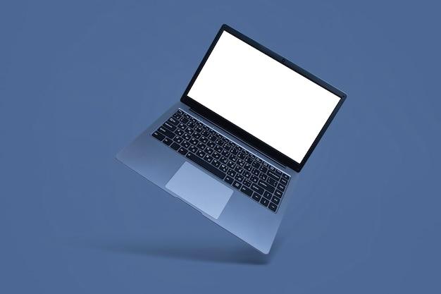 Ordinateur portable moderne et mince avec maquette d'écran blanc sur fond gris avec ombre.