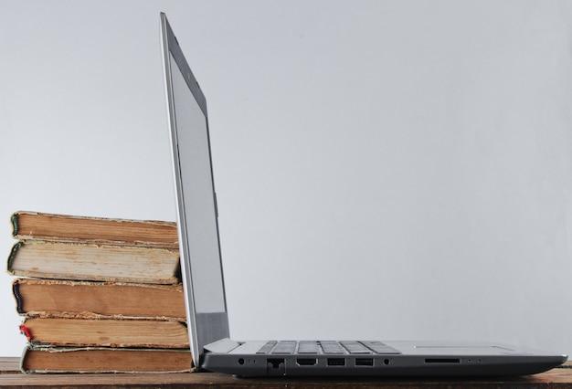 Ordinateur portable moderne et pile de vieux livres sur une étagère en bois contre la surface du mur blanc.