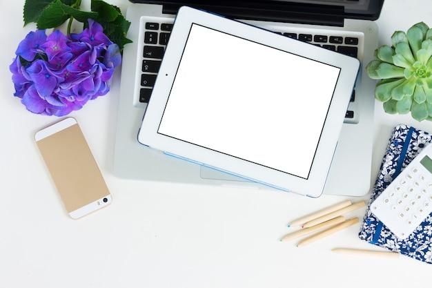 Ordinateur portable moderne, téléphone et tablette sur tableau blanc sur écran blanc