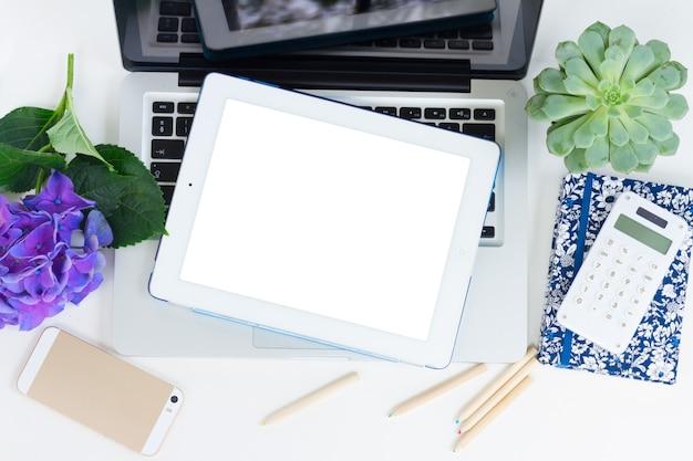 Ordinateur portable moderne, téléphone et tablette sur tableau blanc sur écran vide