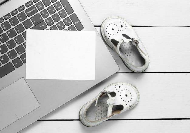 Ordinateur portable avec morceau de papier blanc pour copier l'espace et sandales pour enfants sur bois