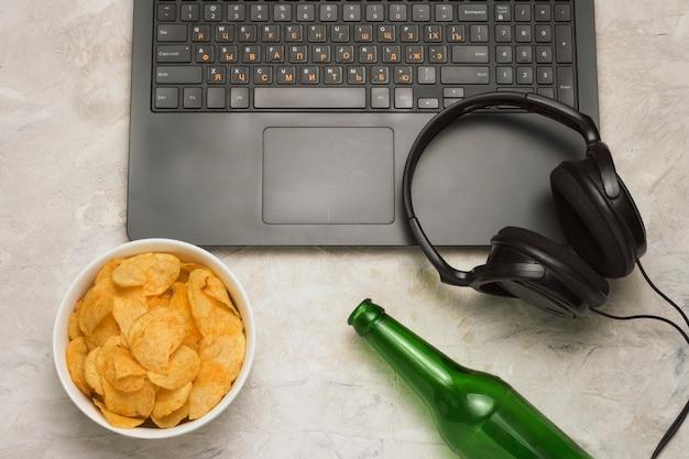 Ordinateur portable noir et casque noir, un bol avec des frites et une bouteille de bière sur une surface en pierre claire. mise à plat, vue de dessus