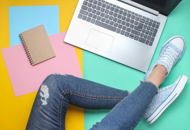 Ordinateur portable, ordinateur portable, jambes féminines en jeans et baskets, style plat