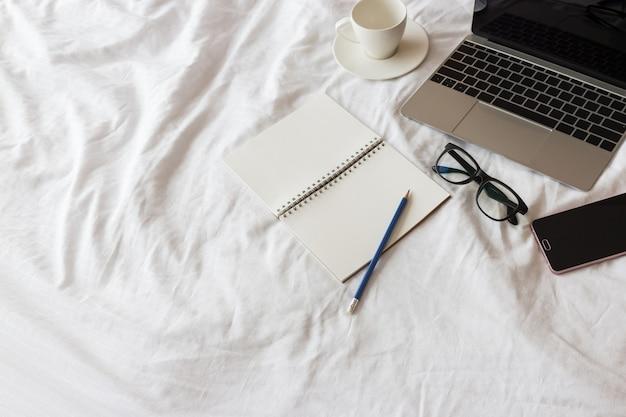 Ordinateur portable, ordinateur portable, téléphone intelligent, lunettes et une tasse de café sur le lit blanc dans la matinée.