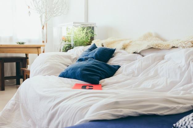 Ordinateur portable et oreillers allongé sur le lit