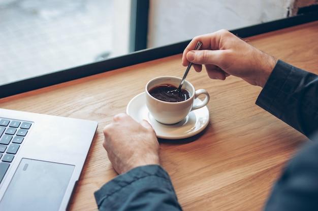 Ordinateur portable ouvert et mains d'hommes avec une tasse de café sur la table dans le café