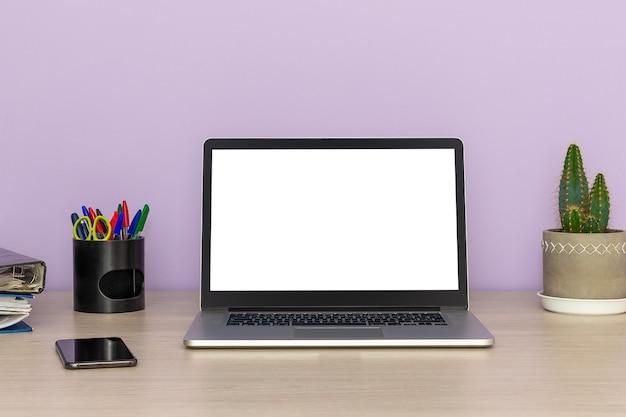 Ordinateur portable ouvert avec smartphone, cactus et dossiers d'affaires sur une table en bois contre un mur lilas, concept de travail de bureau