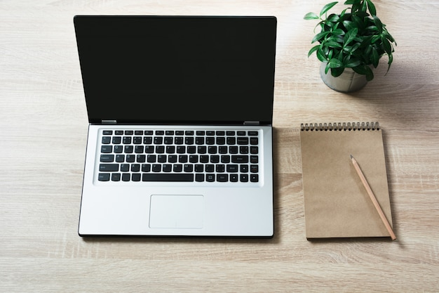 Ordinateur portable ouvert sur la table de bureau en bois de bureau.