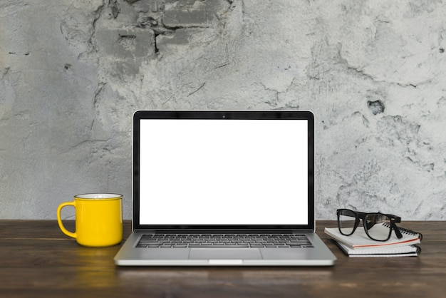 Ordinateur portable ouvert; tasse de café jaune; spectacle; et journal sur la table en bois avec fond de mur patiné