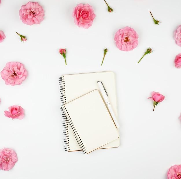 Ordinateur portable avec des pages blanches vierges sur violet et rose avec des pétales
