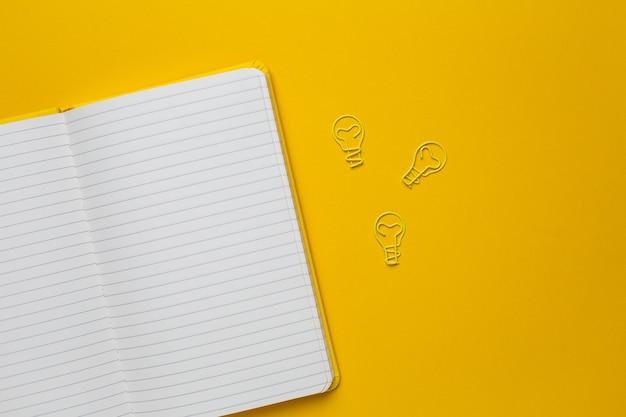 Ordinateur portable avec des pages vierges et idée d'ampoule de trombone sur jaune