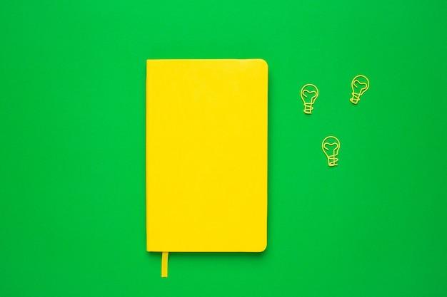 Ordinateur portable avec des pages vierges et idée d'ampoule de trombone sur vert