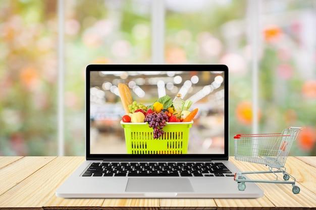 Ordinateur portable et panier sur table en bois avec fenêtre et jardin flou abstrait épicerie en ligne concept