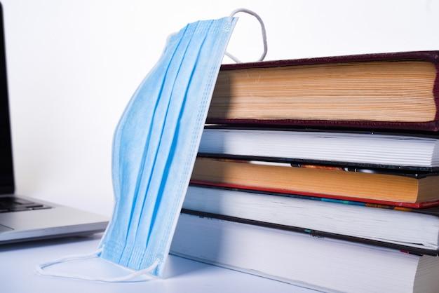 Ordinateur portable, pile de livres et masque médical. isolé. concept d'enseignement à domicile