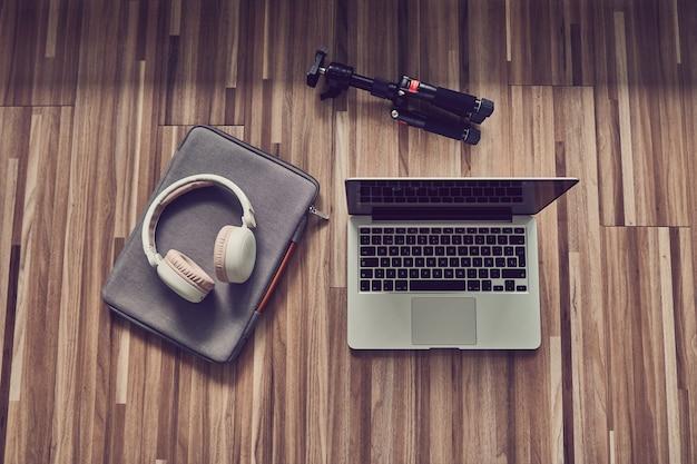 Ordinateur portable sur un plancher en bois à côté d'un casque et d'un trépied