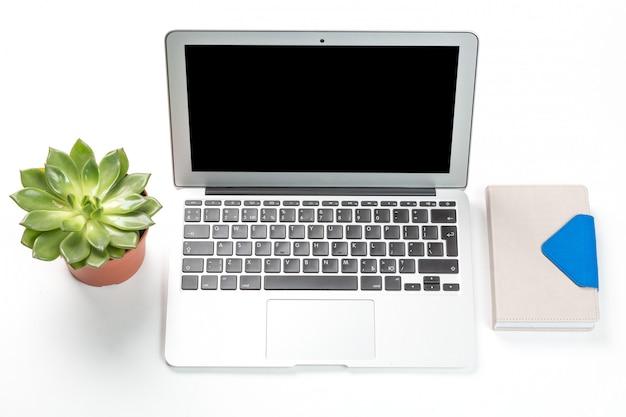 Ordinateur portable avec plante dans un pot et un cahier