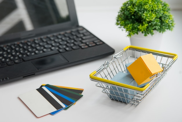 Ordinateur portable, plante verte, panier et cartes de crédit. achats en ligne et conception de livraison photo horizontale