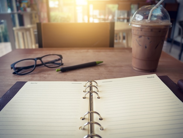 Ordinateur portable (portable) avec une tasse de café glacé et un bloc-notes avec un stylo sur une vieille table en bois.