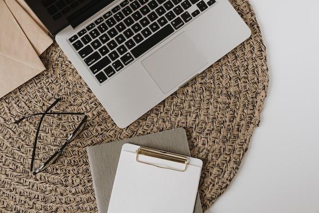 Ordinateur portable, presse-papiers, enveloppe sur fond de rotin. mise à plat, vue de dessus pigiste minimaliste esthétique, espace de travail de bureau à domicile de blogueur.