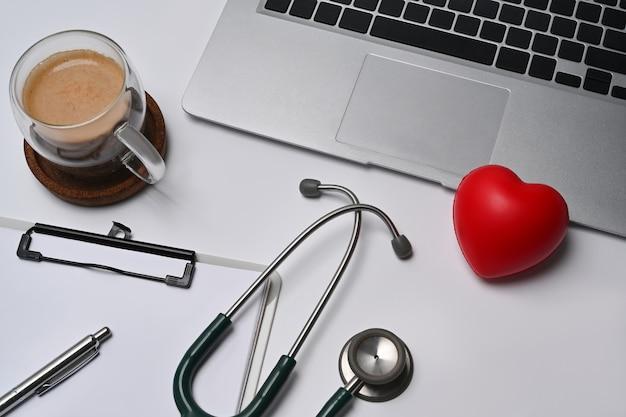 Ordinateur portable, presse-papiers, stéthoscope et coeur rouge sur fond blanc. concept d'assurance maladie.