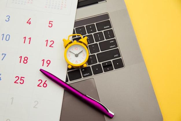 Ordinateur portable et réveil, calendrier mensuel sur fond jaune. le temps s'enfuit.