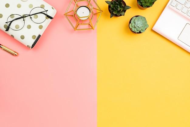 Ordinateur portable rose, fleurs succulentes, verres, stylo et bougie sur table rose et jaune pastel.