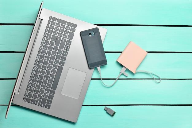 Ordinateur portable, smartphone, banque d'alimentation, clé usb sur une table en bois bleue. appareils et gadgets numériques modernes. vue de dessus.