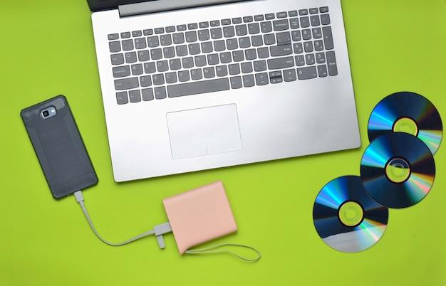 Ordinateur portable, smartphone, banque d'alimentation, lecteurs de cd, sur fond vert. médias numériques, gadgets.