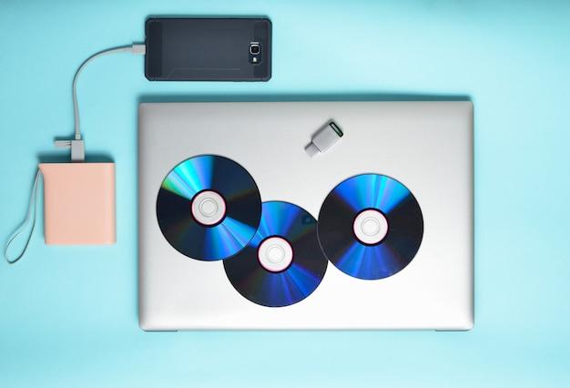Ordinateur portable, smartphone, banque d'alimentation, lecteurs de cd, lecteur flash usb sur fond bleu. médias et gadgets numériques modernes et obsolètes.