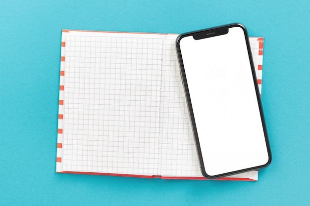 Ordinateur portable avec smartphone avec écran blanc sur fond bleu vue de dessus